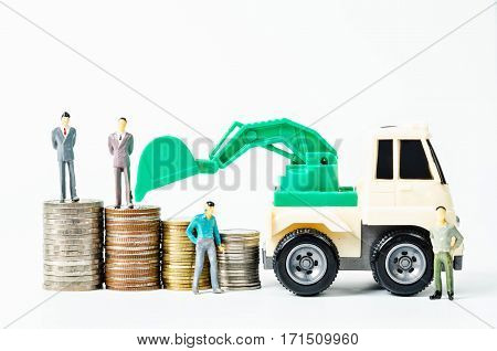 Stack of coins money and backhoe loader toy with business man miniature on white background.
