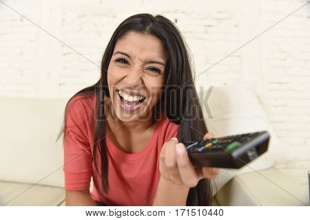 young beautiful and attractive latin woman at home sofa couch laughing and smiling happy watching television comedy movie or funny tv series alone expressive face emotion