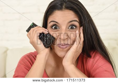 close up portrait young beautiful Spanish woman home watching television on couch at living room happy and excited enjoying tv comedy movie having fun intense face expression