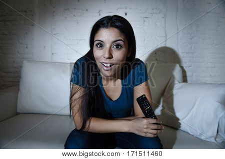 young beautiful Spanish woman in jeans home alone watching television smiling sitting at sofa couch on living room happy and excited enjoying TV show or movie relaxed in dark light