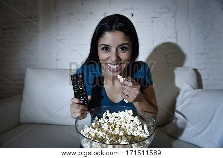 young beautiful latin woman home alone watching television smiling sitting at sofa couch on living room happy and excited enjoying TV show or movie relaxed in dark light eating popcorn
