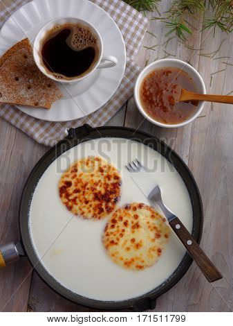 Finnish breakfast with mini farmer cheeses in an iron cooking pan, cloudberry jam, and a cup of coffee
