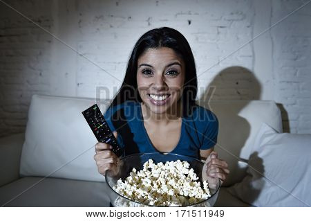 young beautiful Spanish woman home alone watching television smiling sitting at sofa couch on living room happy and excited enjoying TV show or movie relaxed in dark light eating popcorn