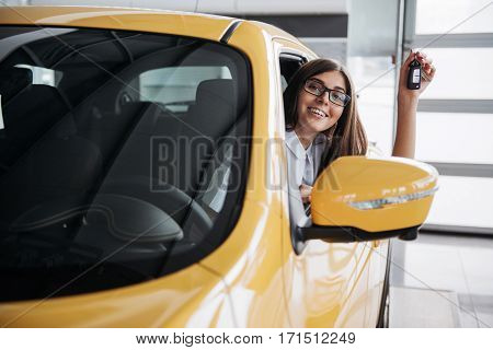 The woman driver smiling showing new car keys.
