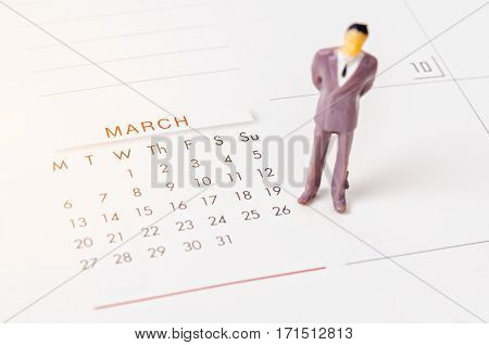 Close up March 2017 calendar page with business people miniatrue. Management time concept.