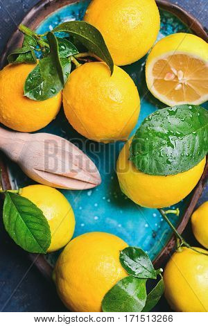Close-up of freshly picked wet lemons with leaves in bright blue ceramic plate, top view, vertical composition