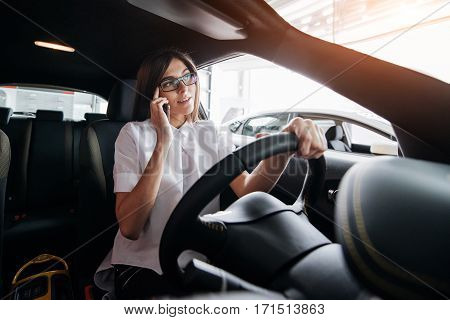 Businesswoman talking on the phone in the car.