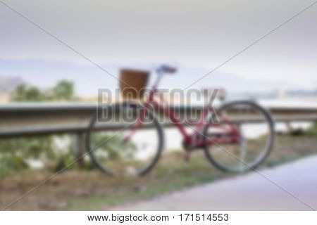 Vintage red bicycle beside river road stock photo