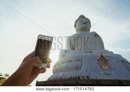 Hands tourist with telephone smartphone to take photographs attractions Big Buddha in Thailand.