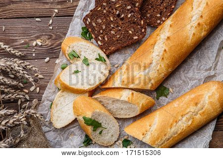 Photo of baguette , bread on table with seeds and herbs