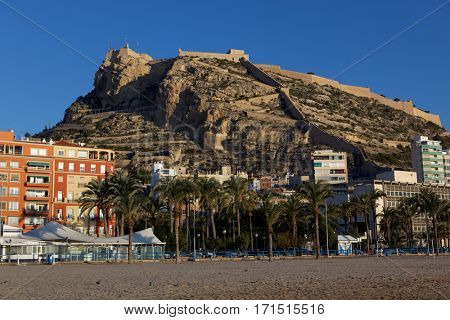 ALICANTE, SPAIN - JANUARY 8, 2013: View to Santa Barbara castle from the beach. Situated on the slopes of Mount Benacantil, the castle originated in IX century