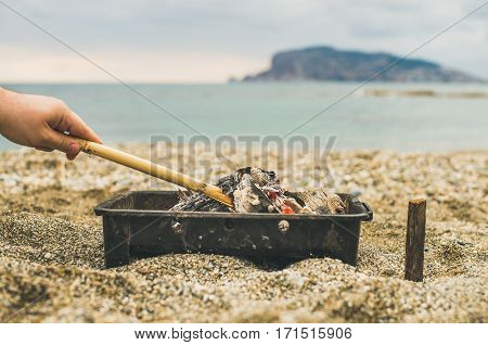Mangal with burning coal at the sea coast and man's hand holding wooden stick , Alanya, Antalya, Mediterranean Turkey. Picnic or outdoor gathreing concept