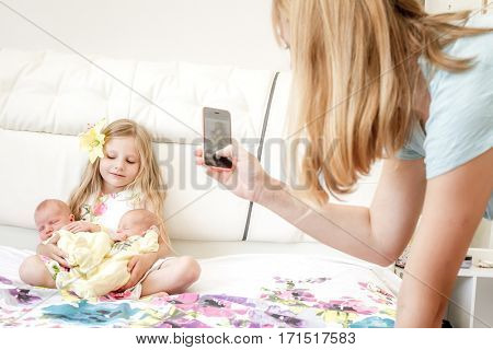 mother taking photo of her daughter and two twin newborn babies at home