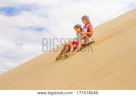 happy mother and son sliding a board on sand dunes, family fun
