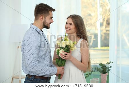 Handsome young man giving bouquet of flowers to his girlfriend at home