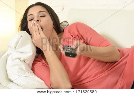 close up portrait of young latin woman sitting at home sofa couch in living room watching television looking tired and bored disappointed holding remote control yawning in negative emotion