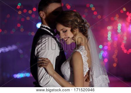 Cute happy wedding couple dancing against defocused lights