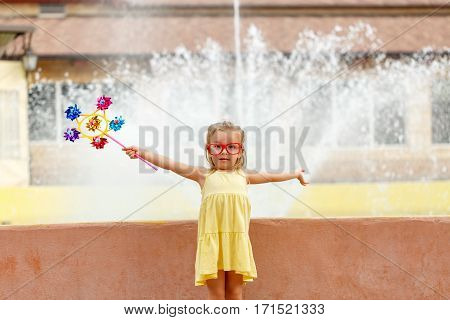 Nice little girl holding a pinwheel in hand. A walk in the summer park near the city fountain. Summer vacation. Outdoor Activities.