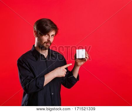 Man holding an empty cube. Advertising Space. Attractive man shows space for copy. Forefinger. He explains something