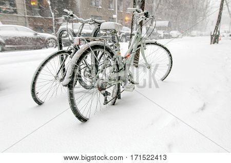 Two bicycles chained to a rack outside are covered in snow during a snowfall in Manhattan.