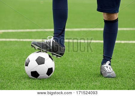 Football player holding ball with foot, closeup