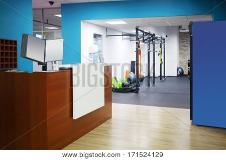 Empty stylish reception with wooden counter and blue walls in fitness center