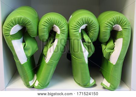 Two pairs of green leather boxing gloves on white shelf in sport center
