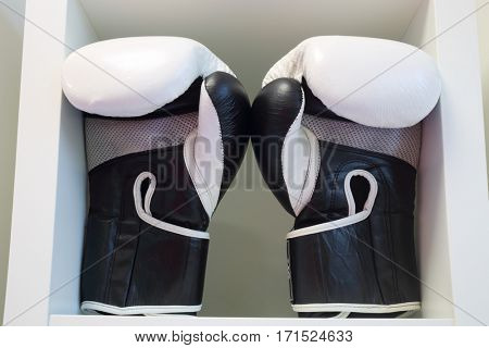 Pair of black and white leather boxing gloves on white shelf in sport center