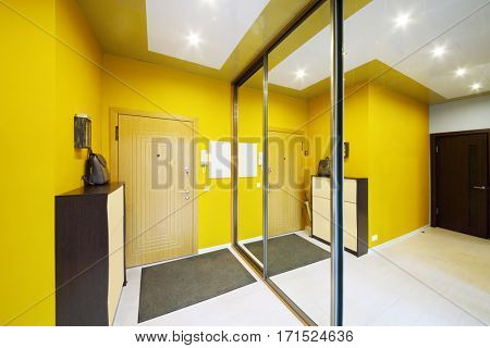 Empty stylish hallway in home with big mirror and yellow walls