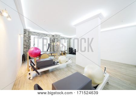 White hall with modern equipment for pilates training - fitballs and trainers