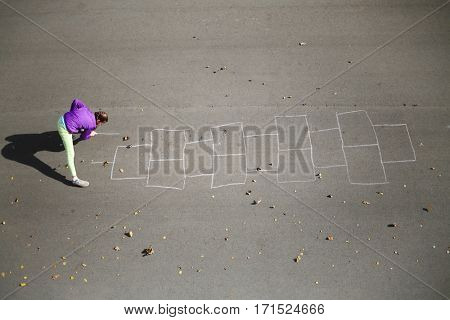 Girl draws by chalk hopscotch on asphalt at autumn day, top view