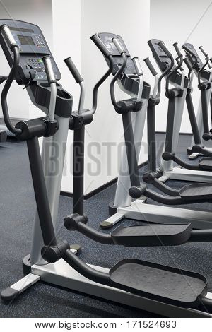 Four new elliptical trainers in modern hall for fitness with white walls