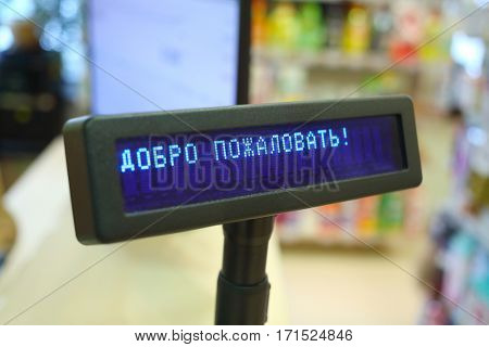Cash register in store, text - Welcome, goods for home are on shelves out of focus