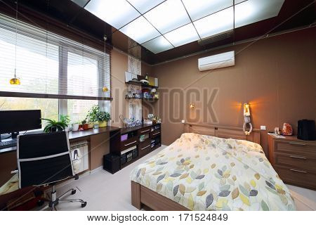 Cozy empty modern bedroom with double bed with workplace and luminous ceiling