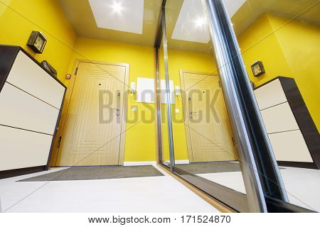 Empty stylish hallway in apartment with big mirror and yellow walls