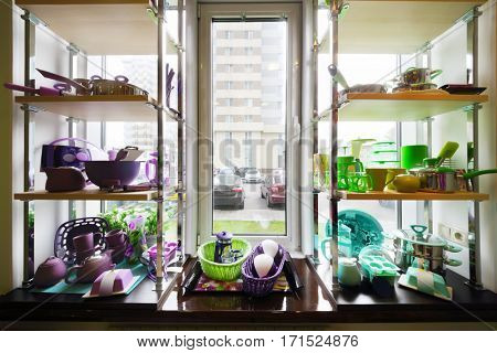 Bright dishes are on shelves on windowsill in Good for Home shop