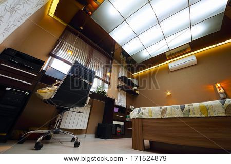 Cozy empty modern bedroom with bed with workplace and luminous ceiling, under view