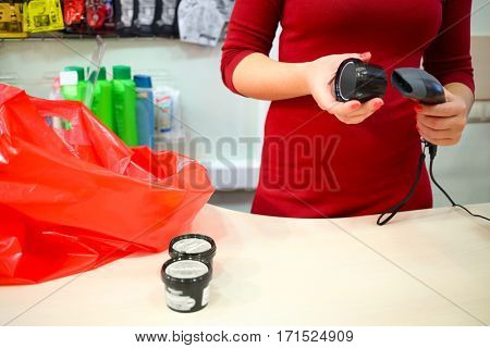 Red bag, female hands register purchase, plastic jars are on table in supermarket, noface
