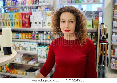 Smiling woman in red dress poses in supermarket Goods for Home