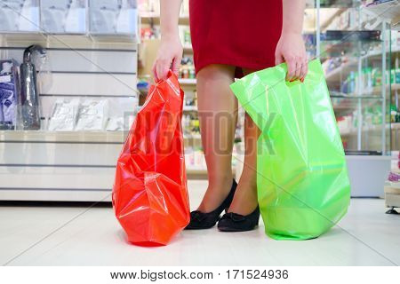 Lags of woman in red with two bags in modern supermarket with many goods