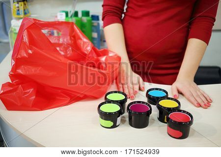 Red bag, female hands and plastic jars are on table in supermarket, noface