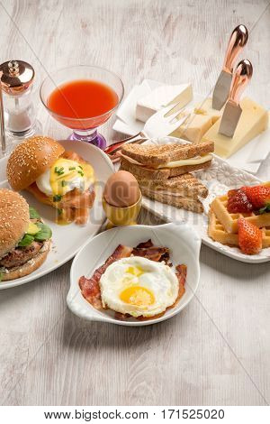 mixed brunch with benedict eggs, waffles, sandwiches and hamburgers
