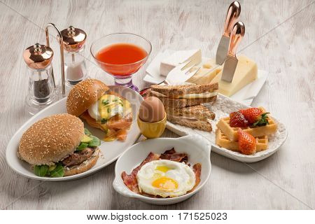 mixed brunch with benedict eggs, sandwiches, waffles and hamburgers
