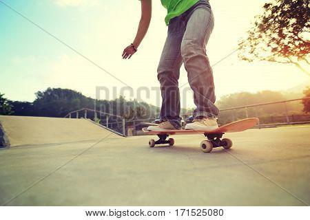 young woman skateboarder legs skateboarding at skatepark