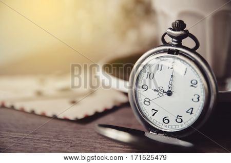 vintage pocket watch on table with old paper