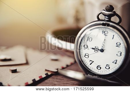 vintage pocket watch on wood table and old paper