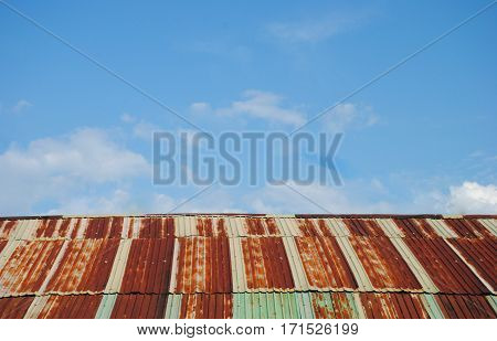 Old rusted and weathered steel quonset hut roof against a blue sky with fluff clouds