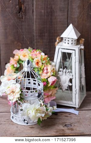Decorative flower wreath and decorative lanterns on wooden background. Selective focus. Place for text.