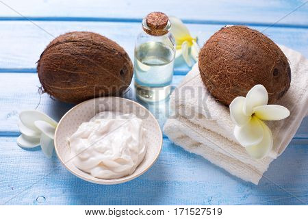 Organic spa products with coconut oil. Coconut coconut oil and cream on blue wooden background. Selective focus.