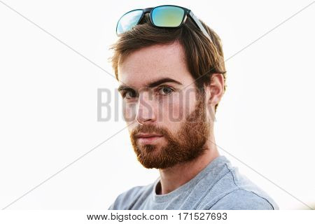 Head and shoulders shot of a young caucasian adult male wearing trendy sunglasses, looking into the camera with a moderate beard to suit his serious persona.